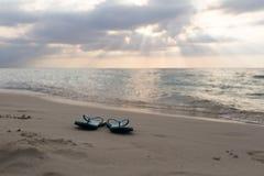 Setzen Sie Pantoffel auf dem Sand in Sonnenuntergang und Meer auf den Strand Lizenzfreies Stockfoto