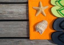 Setzen Sie Pantoffel, Tuch und Starfish auf hölzernem Hintergrund auf den Strand Stockfotos
