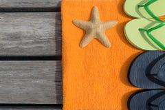 Setzen Sie Pantoffel, Tuch und Starfish auf hölzernem Hintergrund auf den Strand Stockfotografie
