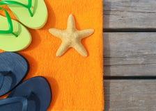 Setzen Sie Pantoffel, Tuch und Starfish auf hölzernem Hintergrund auf den Strand Konzept der Freizeit und der Reise Stockfotos