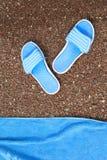 Setzen Sie Pantoffel und ein Tuch auf den Strand, um auf einem Pebble Beach zu liegen Lizenzfreie Stockfotos
