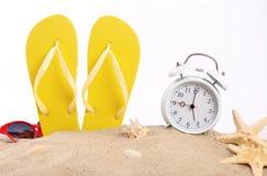 Setzen Sie Pantoffel, Wecker, Sonnenbrille und Muscheln im San auf den Strand Lizenzfreie Stockfotos