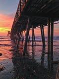 Setzen Sie Pier bei buntem Sonnenuntergang mit Reflexionen im Wasser auf den Strand Stockbild