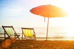 Setzen Sie Ruhesessel auf verlassenem Küstenmeer bei Sonnenaufgang auf den Strand Reise Lizenzfreie Stockfotos