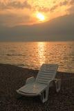 Setzen Sie Ruhesessel bei Sonnenuntergang, garda See, Italien auf den Strand Lizenzfreies Stockfoto