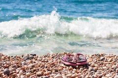 Setzen Sie Schuhe auf den Seekieseln in den Wellen auf den Strand Stockfotos