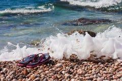 Setzen Sie Schuhe auf den Seekieseln in den Wellen auf den Strand Lizenzfreie Stockfotografie