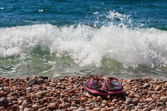 Setzen Sie Schuhe auf den Seekieseln in den Wellen auf den Strand Lizenzfreie Stockfotos
