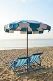 Setzen Sie Segeltuchbetten mit blauem und weißem Regenschirm auf den Strand Lizenzfreie Stockfotos