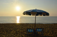 Setzen Sie Segeltuchbetten mit blauem und weißem Regenschirm auf den Strand Lizenzfreie Stockfotografie