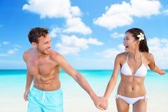 Setzen Sie Paare des Ferienspaßes in der Bikinibadebekleidung auf den Strand Stockfotos