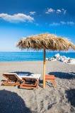 Setzen Sie Sonnenbetten und Strohregenschirm auf schwarzem Strand in Santorini-Insel, Griechenland auf den Strand Stockbild