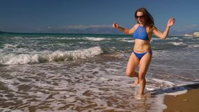 Setzen Sie sorglosen Betrieb der Bikinifrau entlang dem Wasser auf dem Strand auf den Strand Malerische Seeküste von Korfu, Griec stock footage