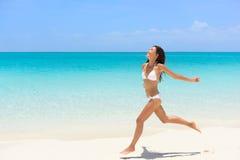 Setzen Sie sorglosen Betrieb der Bikinifrau im Freiheitsspaß auf den Strand Stockbilder