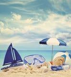 Setzen Sie Spielwaren auf sandigem Strand mit blauem Meer auf den Strand Stockbild