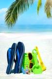 Setzen Sie Spielwaren und Flipflops im Sand auf den Strand Lizenzfreie Stockfotografie