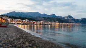 Setzen Sie in Stadt Giardini Naxos am Sommerabend auf den Strand Lizenzfreie Stockfotografie