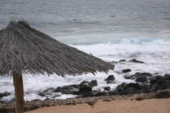 Setzen Sie Strohregenschirm auf den Strand Stockbilder