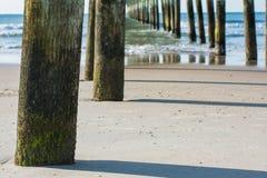 Setzen Sie Szene, Abschluss oben von Strandpierbeiträgen auf den Strand Stockfotos
