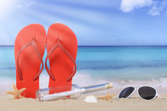 Setzen Sie Szene mit Flipflopsandalen und -Flaschenpost im Sommer VA auf den Strand lizenzfreies stockbild