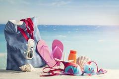 Setzen Sie Tasche auf den Strand und setzen Sie Einzelteile, Ferienhintergrund auf den Strand Lizenzfreie Stockfotografie