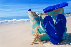 Setzen Sie Tasche mit Flipflops durch den Ozean auf den Strand Lizenzfreies Stockbild