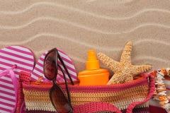 Setzen Sie Tasche mit Flipflops, Sonnenbrille und Lichtschutz auf den Strand Zubehör für den Strand Lizenzfreie Stockfotografie