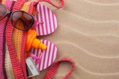 Setzen Sie Tasche mit Lichtschutz, Flipflops, Mobiltelefon, Sonnenbrille auf den Strand Stockfotografie