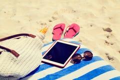 Setzen Sie Tasche, Pantoffel und Notenauflage auf dem Strand auf den Strand Stockfoto