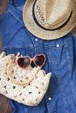 Setzen Sie Tasche, Sonnenbrille und Hut auf hölzernem Hintergrund auf den Strand Lizenzfreie Stockfotos