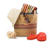 Setzen Sie Tasche und Tuch mit dem ein Sonnenbad nehmenden Zubehör auf den Strand, das auf Weiß lokalisiert wird Lizenzfreie Stockfotos