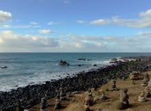 Setzen Sie Ufer voll von den Monolithen auf den Strand, die mit flachen Steinen mit Seehintergrund gemacht werden Stockfotos