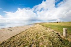 Setzen Sie und ein Graben entlang einer niederländischen Mündung auf den Strand Stockbild