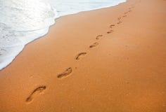 Setzen Sie, Welle und Abdrücke zur Sonnenuntergangzeit auf den Strand Stockbild
