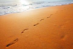 Setzen Sie, Welle und Abdrücke zur Sonnenuntergangzeit auf den Strand Stockfoto