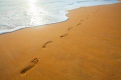 Setzen Sie, Welle und Abdrücke zur Sonnenuntergangzeit auf den Strand Lizenzfreies Stockbild
