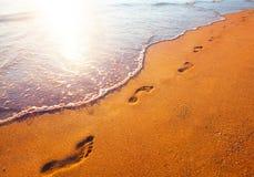 Setzen Sie, Welle und Abdrücke zur Sonnenuntergangzeit auf den Strand lizenzfreie stockfotos
