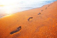 Setzen Sie, Welle und Abdrücke zur Sonnenuntergangzeit auf den Strand lizenzfreie stockfotografie