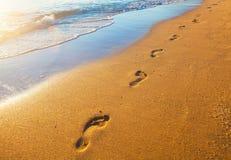 Setzen Sie, Welle und Abdrücke zur Sonnenuntergangzeit auf den Strand Stockbilder