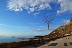 Setzen Sie Whit eine Ansicht über das Meer und den Himmel auf die Bank Lizenzfreie Stockfotos
