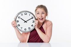 Setzen Sie Zeit Konzeptes für die begeisterte junge Frau fest, die Uhr hält Stockbilder