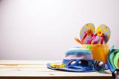 Setzen Sie Zusatz, Hut, Sonnenbrille, Schuhe, Regenschirm auf hölzernem, Konzept auf den Strand Stockbilder