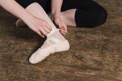 Setzen von Ballettschuhen stockbild