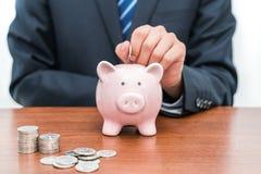 Setzen von Münzen in piggy Bank-Dkonzept von Einsparungen stockfoto
