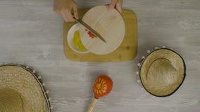 Setzt Lebensmittel in den Teller mit einem Messer ein Ist auf dem Tisch die zwei mexikanischen Hüte, maracas, Abstraktion für ins Lizenzfreie Stockfotos