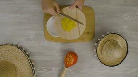 Setzt Lebensmittel in den Teller mit einem Messer ein Ist auf dem Tisch die zwei mexikanischen Hüte, maracas, Abstraktion für ins Lizenzfreie Stockfotografie