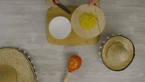 Setzt Lebensmittel in den Teller mit einem Messer ein Ist auf dem Tisch die zwei mexikanischen Hüte, maracas, Abstraktion für ins Lizenzfreie Stockbilder
