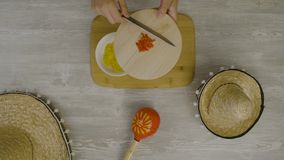 Setzt Lebensmittel in den Teller mit einem Messer ein Ist auf dem Tisch die zwei mexikanischen Hüte, maracas, Abstraktion für ins Stockfotografie