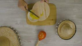 Setzt Lebensmittel in den Teller mit einem Messer ein Ist auf dem Tisch die zwei mexikanischen Hüte, maracas, Abstraktion für ins Lizenzfreies Stockfoto