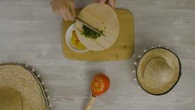 Setzt Lebensmittel in den Teller mit einem Messer ein Ist auf dem Tisch die zwei mexikanischen Hüte, maracas, Abstraktion für ins Stockbilder